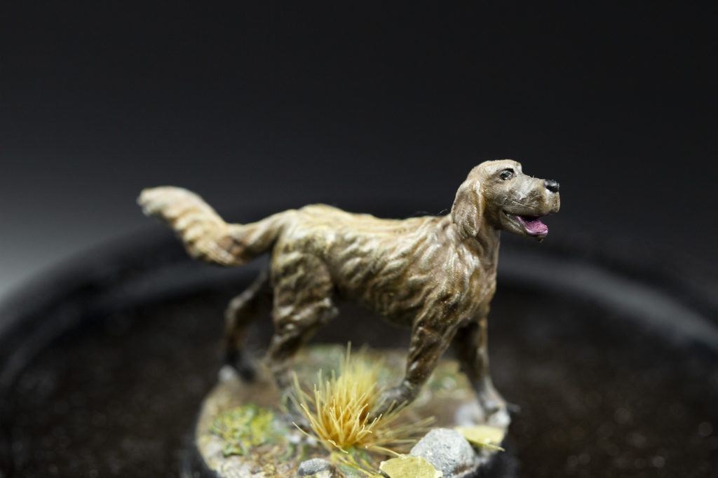 Photo of printed 3d miniature dog. His fur became highlighted over drybrushing.