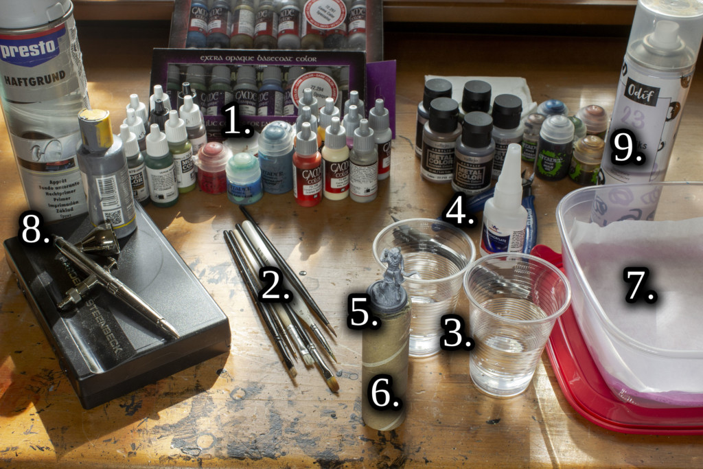All items needed to paint your 3d miniatures or sculptures. Paints, washes, brushes, two cups of water, clippers, superglue, handle, waterpad, spray primer and varnish.