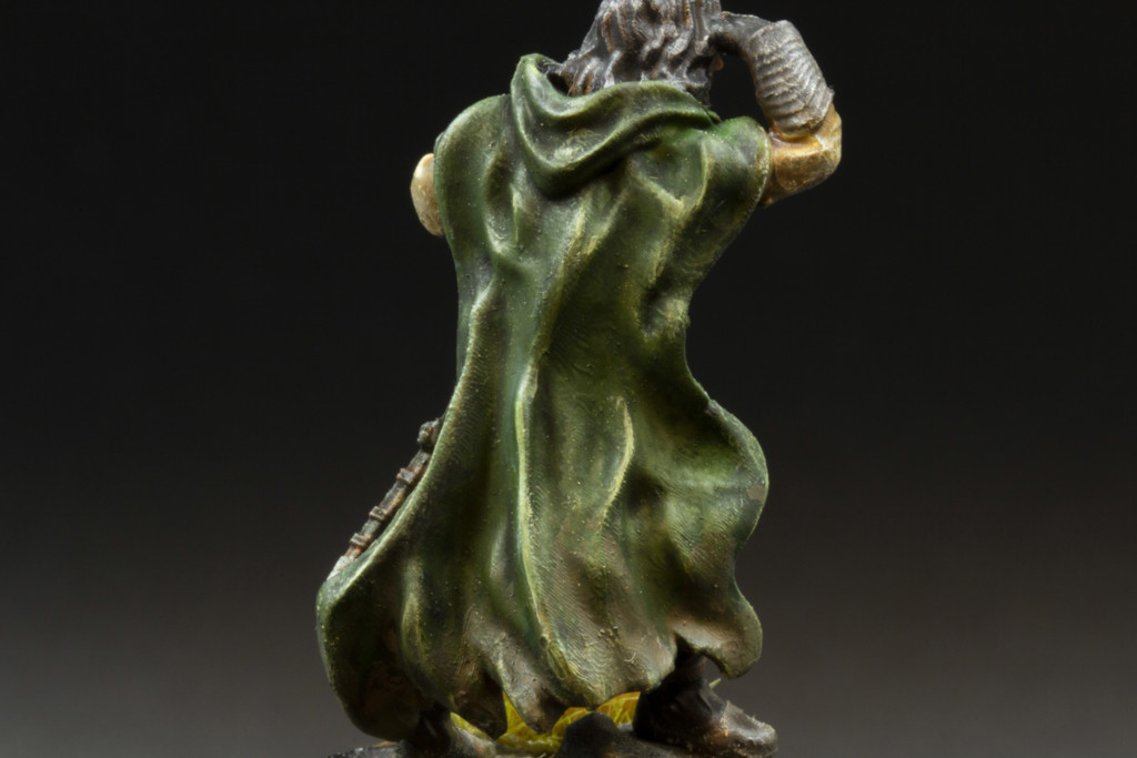 The classical highlighting effect showed on the printable 3d miniature. Fantasy character standing backwards with highlightings on his green cloak.