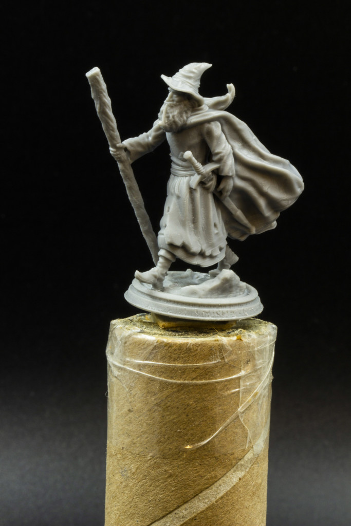 A wizard with a wand, sword and a pointed hat on his head stands on handmade handle made of paper towel tube.